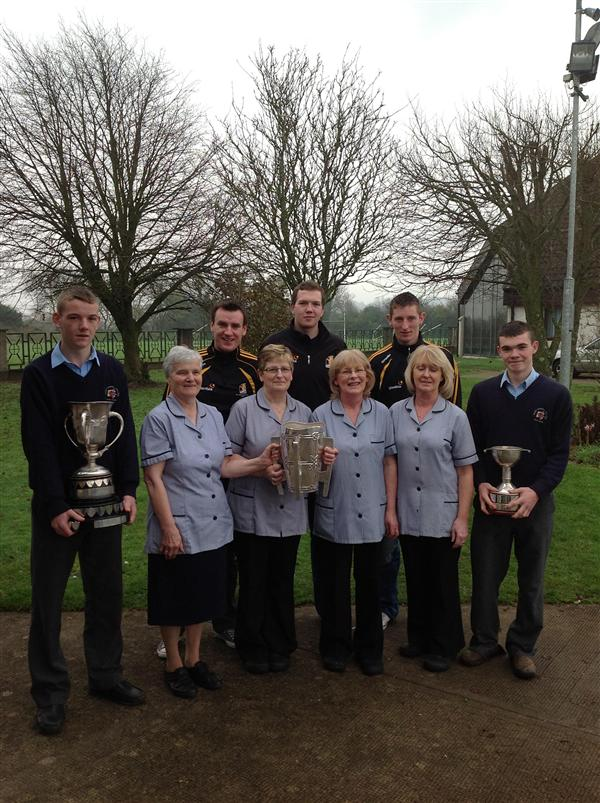 Members of the dining room staff with students,Daire Barden and Joe Sutton, holding the Leinster'A' U-14 and U-16 trophies